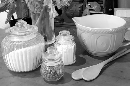 Baking ingredients, mixing bowl and wooden spoons.